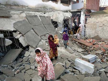 children_walking_through_the_debris_of_what_was_a_school